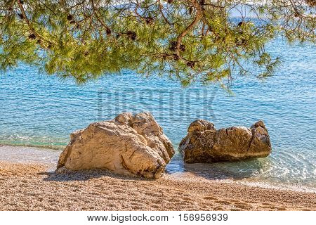 Two large stones by the sea on the Tucepi town beach.