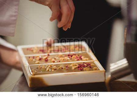 Worker sprinkling confectionary on chocolate mould in factory