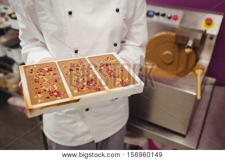 Mid section of worker holding chocolate mould in kitchen