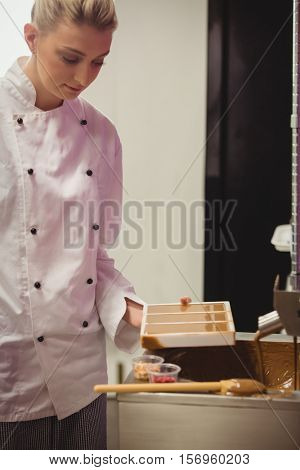 Worker holding chocolate mould in factory