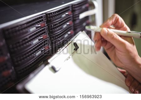 Close-up of technician maintaining record of rack mounted server on clipboard in server room