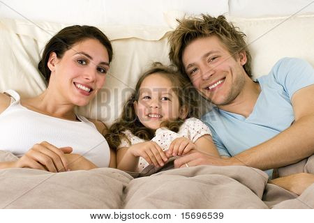 Happy family laying in bed