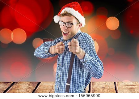 Man in santa hat gesturing against digitally generated background during christmas time