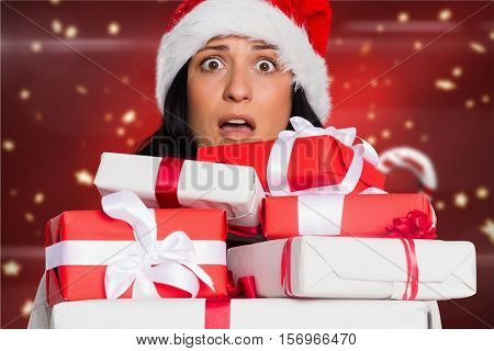 Shocked woman in santa hat holding stack of gift boxes against digitally generated background