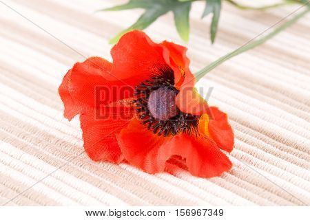 Red fabric poppy on cloth background, close-up picture.