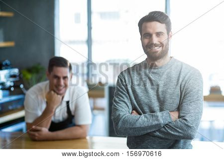 Portrait of man standing with arms crossed at counter Portrait of man standing with arms crossed at counter in café