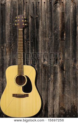 Classic guitar leaning on a wooden fence