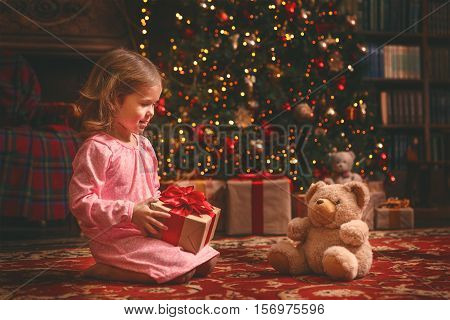 child girl in nightgown with teddy bear in the night at the Christmas tree