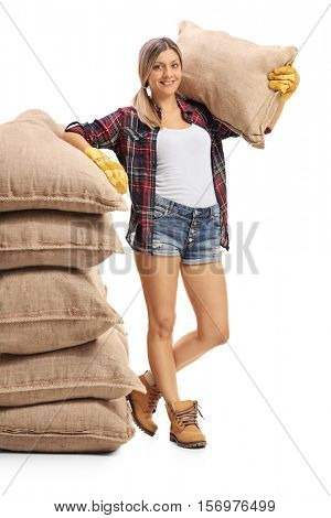 Full length portrait of a female farmer leaning on a pile of burlap sacks and holding a sack on her shoulder isolated on white background