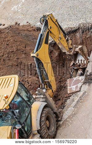 Yellow excavator working with red soil and dusty
