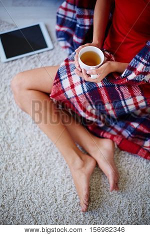 Young woman wrapped in blanket sitting on carpet and warming up with hot tea