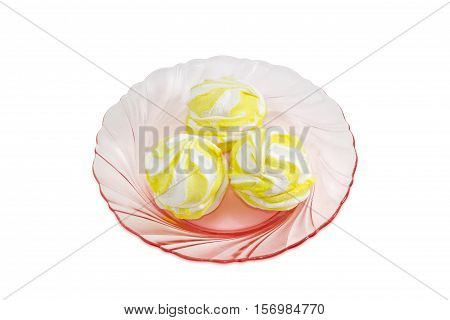 Three soft confectionery - zefir white and yellow color on a pink glass dish on a light background