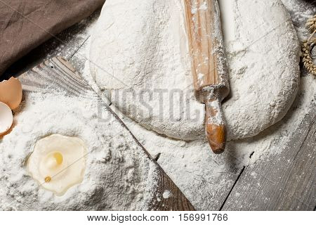 Close up rolling pin with flour eggs and yolk on wooden table top view. Bakery background