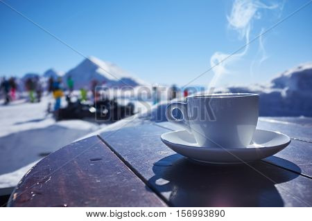Glass cup of tea on wooden table and blurred nature background