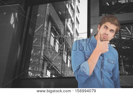 Thoughtful man with hand on chin against exterior of modern building