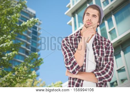 Thoughtful hipster against white background against view of buildings
