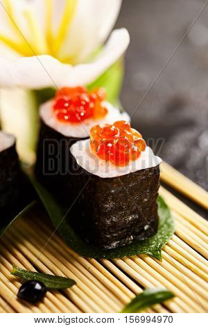 Ikura Maki Sushi - Roll with Cream Cheese inside. Topped with Ikura (Salmon Roe). Sushi Food and Natural Flower Concept