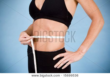 Healthy woman taking her body measurements