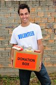 stock photo of charity relief work  - happy volunteer carrying a food donation box - JPG