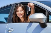 Driving new rental car or drivers license concept. Young teenager woman driver holding car key drivi poster