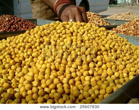 Hand grabbing chick peas in market