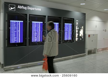 man looking at flight information panel at airport