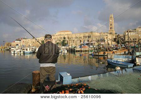 rod fisherman in akko harbour; israel