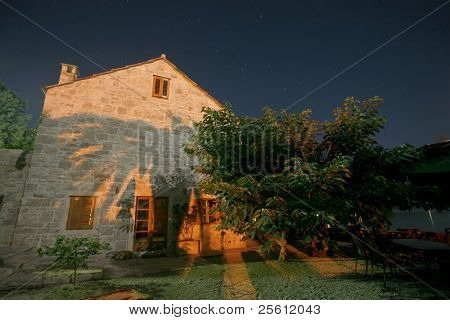 Night shot of house with palm tree shadow casted of wall