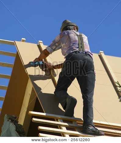 roofer with hat on house roof in summer