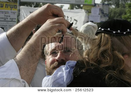 MERON, ISRAEL - MAY 6: Lag Ba'omer pilgrim cuts hair of young boy as a lucky sign May 6, 2007 in Meron. Lag Ba'omer is a Jewish holiday where thousands of Jews make pilgrimage to Meron, Israel.