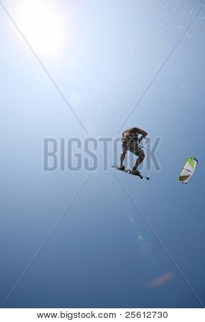 Kite surfer jumping towards the sun with water spray