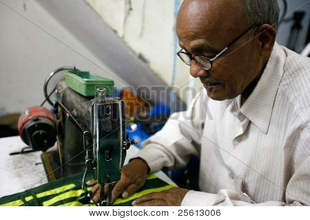 DELHI - FEBRUARY 26: Old man stitching in local Indian factory February 26, 2008 in Dehli, India. Working ages in this factory is from 16 to 71 years old.