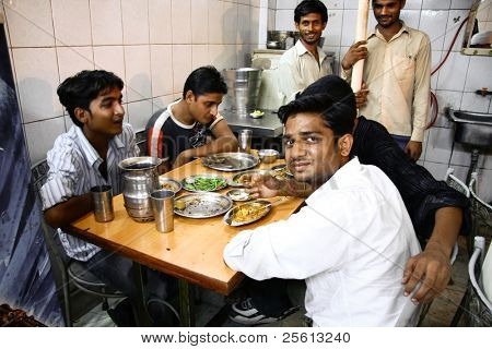 DELHI - SEPTEMBER 19: Young men eating late dinner in street restaurant on September 19, 2007 in Delhi, India. It is common to frequently eat out in India.