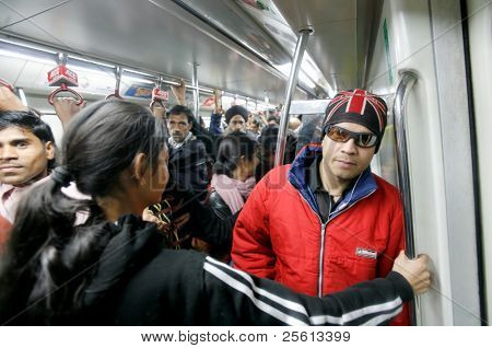 DELHI - JANUARY 19: Men and women standing in crowded train carriage on January 19, 2008 in Delhi, India. Nearly 1 million passengers use the metro daily.