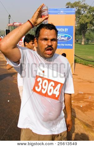 DELHI - OCTOBER 28: Male runner pouring water over head during Half Marathon on October 28, 2007 in Delhi, India. The 2009 event attracted around 29,000 runners of all strengths.
