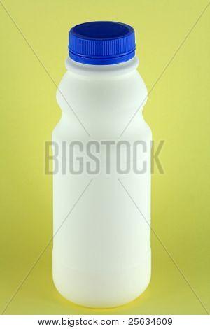 Una botella de leche pasteurizada fresca sobre un fondo amarillo