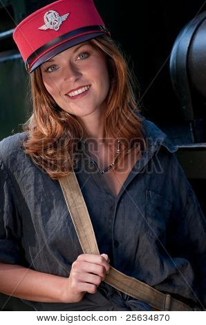 Smiling young woman wearing conductor's cap in front of the locomotive