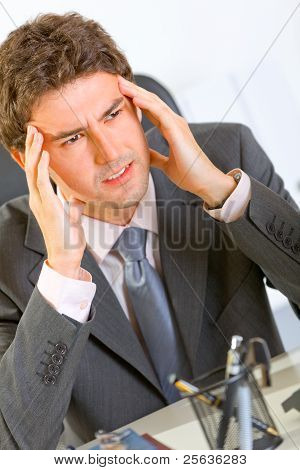 Portrait Of Stressed Modern Businessman Sitting At Office Desk