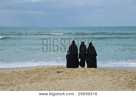Arabic women in abaya staring at the sea.