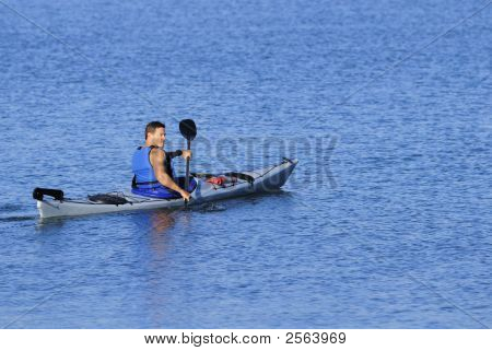 Athletic Kayaker Rows Off