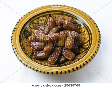 A moroccan bowl full of ripped dates.