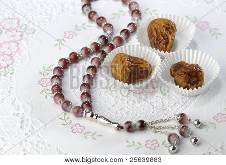Dates in paper cups with islamic rosary.