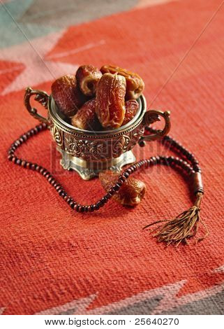 A bowl of dates and an Islamic rosary on a red rug