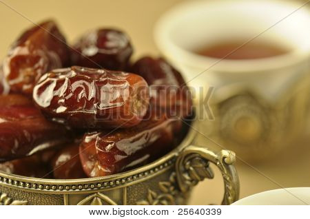 An extreme close up of  golden bowl of dates and tea
