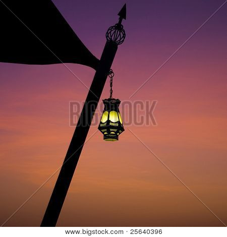 Hanging arabic lamp against colorful sky