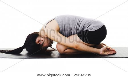 Chinese woman on a yoga mat doing the childs pose.