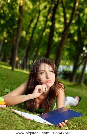 woman laying on grass and thinking