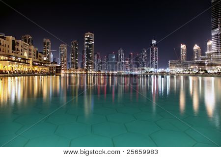 Modern night city of Dubai, with reflection on water surface.