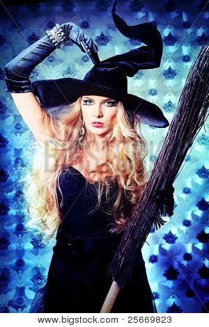 Charming halloween witch with broom over vintage background.