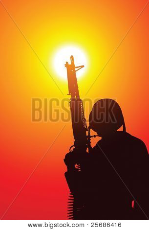 Soldier with a machine gun on sunset
